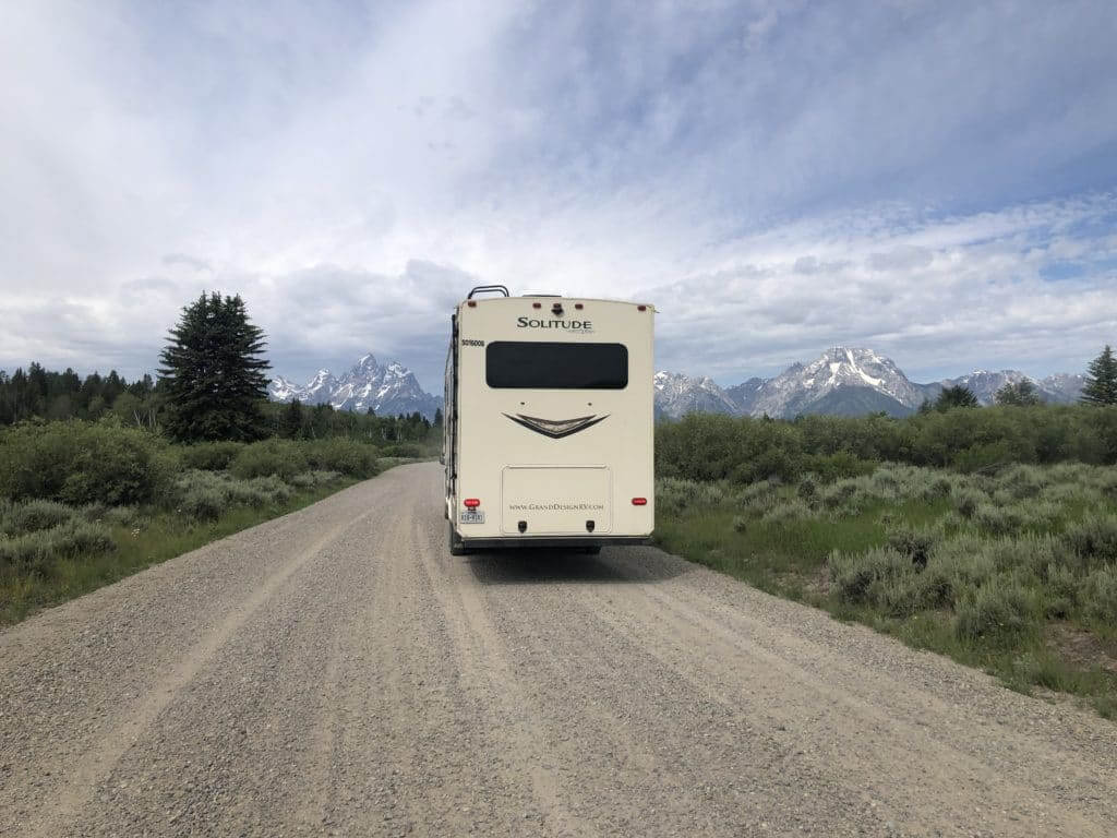 Large picture window in the back of a fifth wheel parked in front of the Grand Tetons