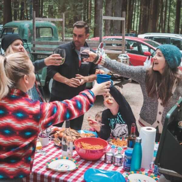 A group of millennial friends toasting a meal at a Good Sam campsite in the forest
