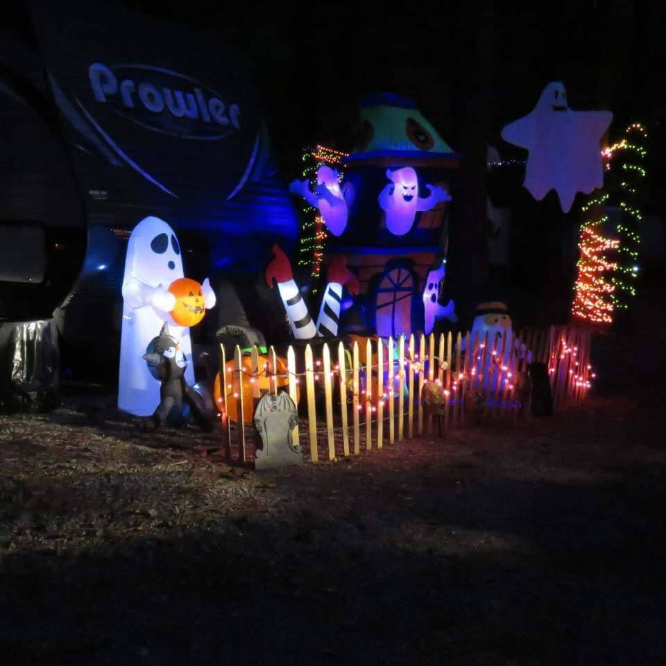 a Prowler travel trailer with orange string lights and a lot of blowup ghosts in the yard.