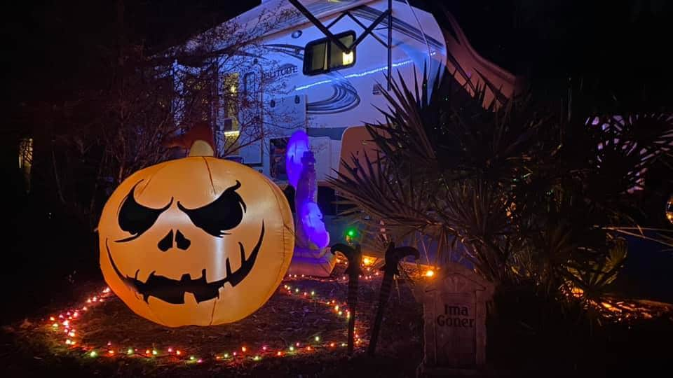Giant blowup carved pumpkin with orange string lights and a Grand Design Solitude RV in the backgound