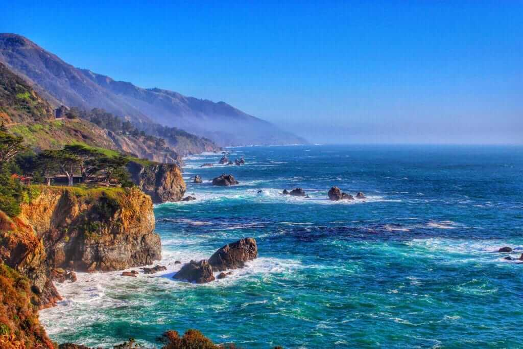 Coastal view of Big Sur with mountains and deep blue ocean crashing against the cliffs, one of the stops on the Pacific Coast Highway Road Trip