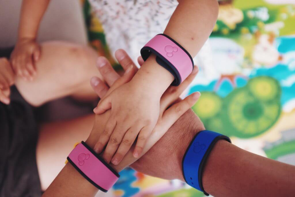 Family with hands in the middle showing their Disney World annual pass bracelets