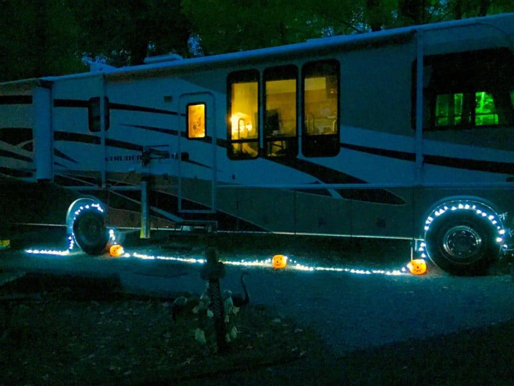 a Motorhome with blue string lights and three orange lightup pumpkins.