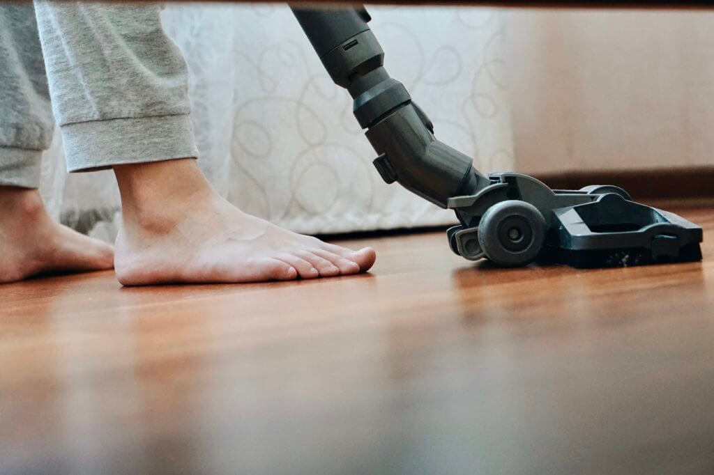 A barefoot person is using a stick vacuum to clean the vinyl floors of the RV after choosing the best corded vacuum for the RV