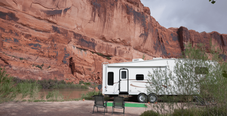 RV dry camping along a river set against a desert red rock wall.