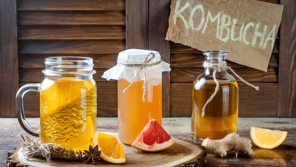 Homemade kombucha tea is shown in containers and also in a drinking mug with a slice of orange.
