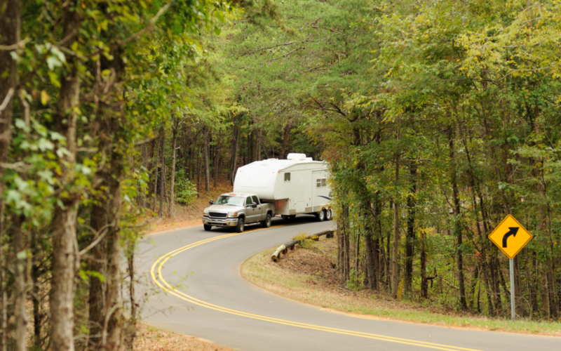 A truck tows a fifth wheel RV through a windy forest road. The truck has a B&W companion hitch so you know the fifth wheel RV is securely hitched.